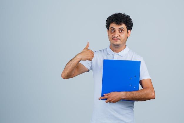 ファイルフォルダを保持し、白いtシャツとジーンズで親指を表示し、幸せそうに見える若い男、正面図。
