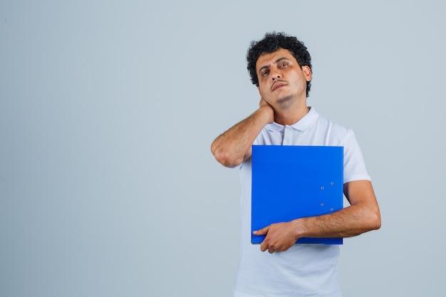 파일 폴더를 들고 흰색 티셔츠와 청바지를 입은 목 뒤에서 손을 잡고 피곤해 보이는 젊은 남자. 전면보기.
