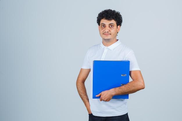 흰색 티셔츠와 청바지에 파일 폴더를 들고 진지한 정면을 바라보는 청년.