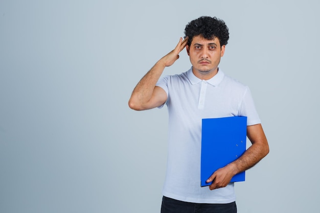 Young man holding file folder, showing salute gesture in white t-shirt and jeans and looking serious. front view.