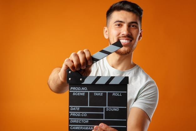 Young man holding film clapper board against yellow