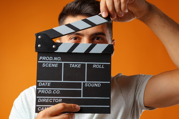 Young man holding film clapper board
