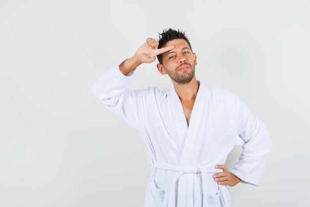 白いバスローブを着て額に指を持って、陽気に見える若い男、正面図。