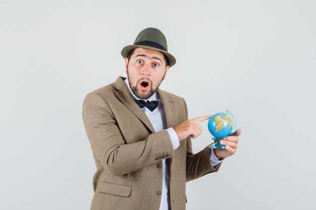 Young man holding finger on world globe in suit, hat and looking amazed. front view.