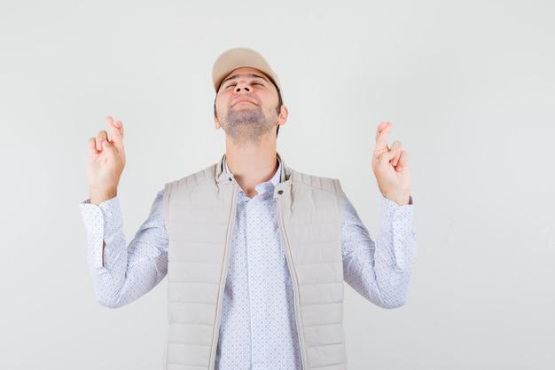 베이지 색 재킷과 모자에 눈을 감고 심각한 찾고있는 동안 손가락을 잡고 머리를 올리는 젊은 남자. 전면보기.