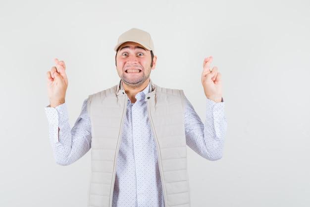 젊은 남자가 손가락을 잡고 베이지 색 재킷과 모자에 넘어 행복, 전면보기를 찾고 있습니다.