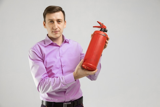 Young man holding a fire extinguisher in his hands