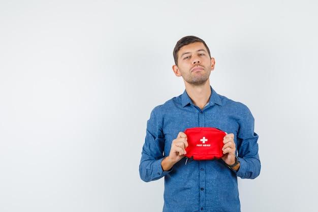 青いシャツを着た救急箱を持って、注意深く見ている若い男。正面図。