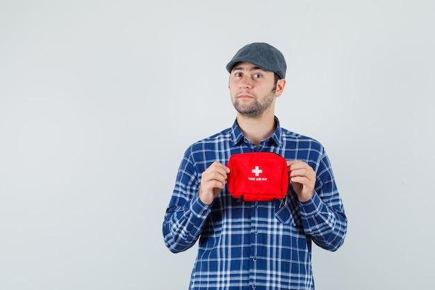 シャツ、キャップで応急処置キットを保持し、自信を持って、正面図を探している若い男。