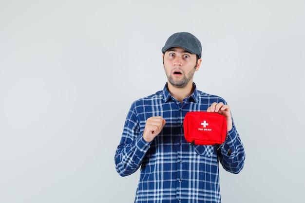 シャツ、キャップで応急処置キットを保持し、驚いたように見える若い男、正面図。