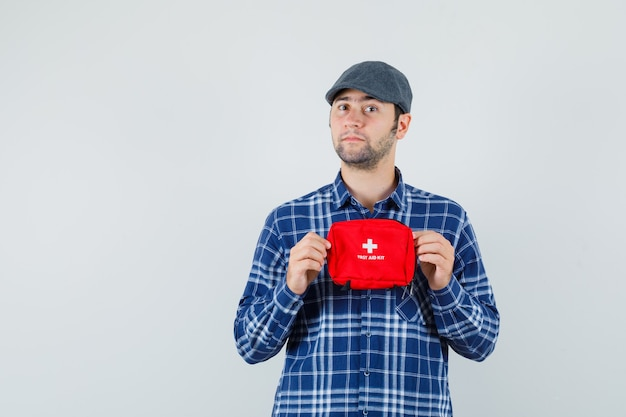 Giovane uomo con kit di pronto soccorso in camicia, berretto e guardando fiducioso, vista frontale.