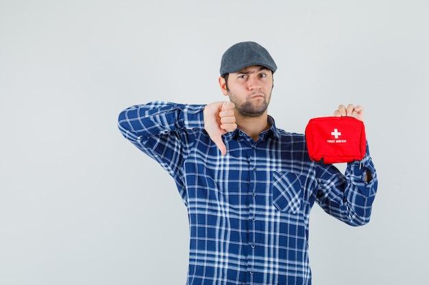 救急箱を持って、シャツに親指を下に向けて、キャップの正面図を示す若い男。