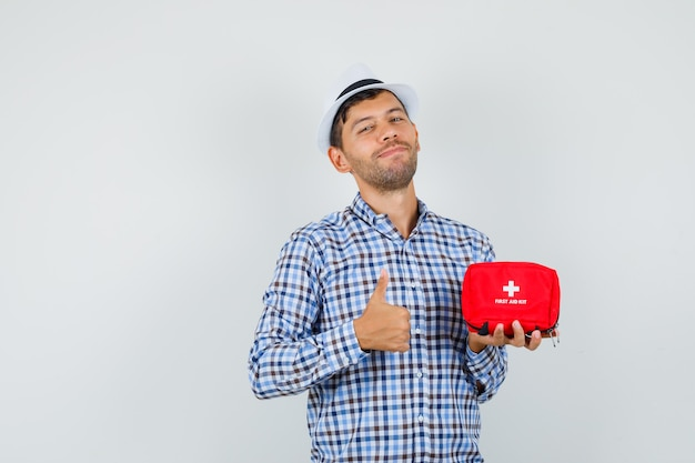 Young man holding first aid kit, showing thumb up in checked shirt, hat and looking optimistic
