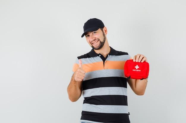 Молодой человек держит аптечку, показывает палец вверх в футболке, кепке и рад. передний план.