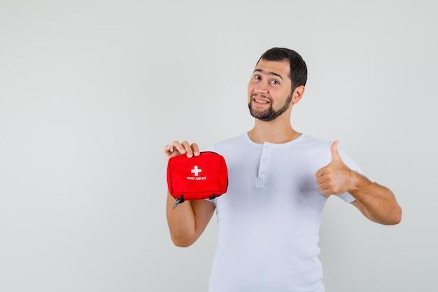 白いtシャツに親指を立てて救急箱を持って、陽気に見える若い男、正面図。テキスト用のスペース