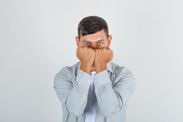 Молодой человек держит кулаки возле лица в рубашке и выглядит уверенно