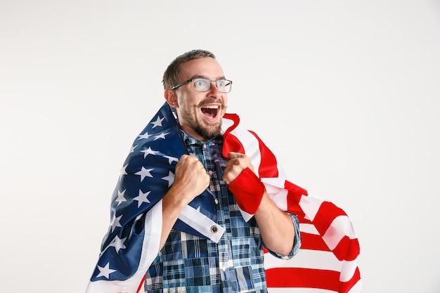 白いスタジオで隔離のアメリカ合衆国の旗を保持している若い男。