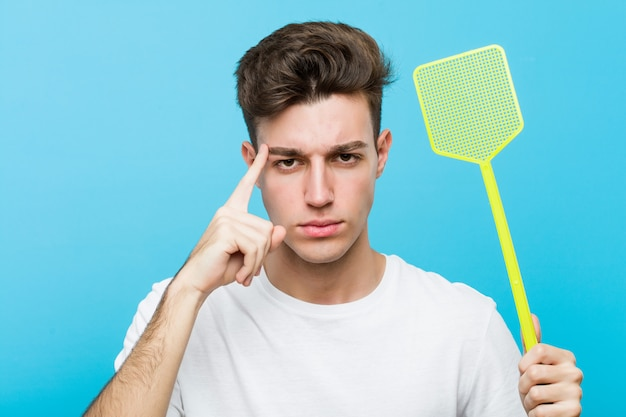 Young man holding a fly swatter pointing his temple with finger, thinking, focused on a task