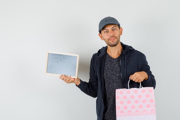 Tシャツ、ジャケット、キャップでフレームとショッピングバッグを保持し、前向きに見える若い男。正面図。