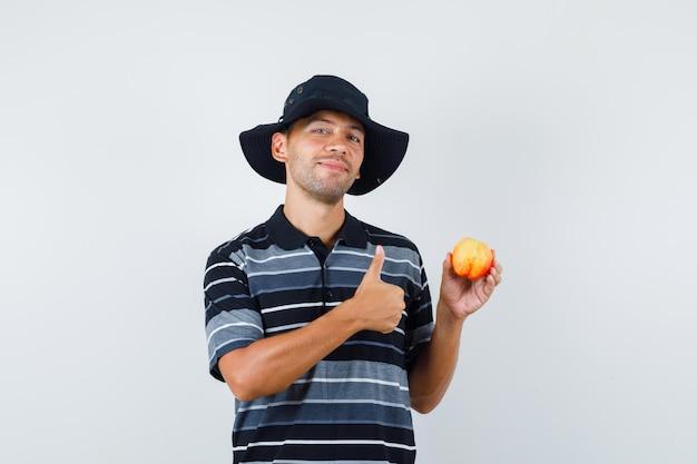 Tシャツ、帽子、陽気に見える親指で新鮮なリンゴを保持している若い男。正面図。