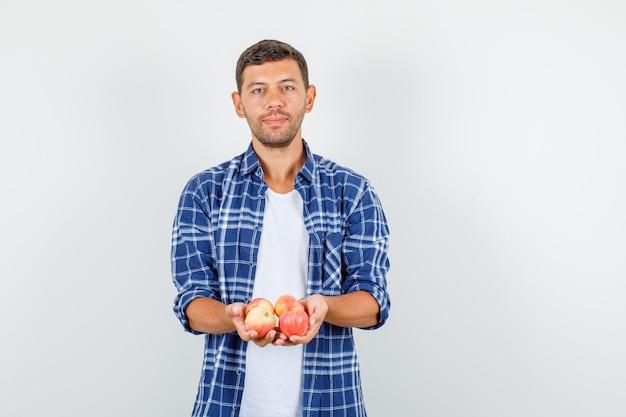 シャツの正面図で新鮮なリンゴを保持している若い男。
