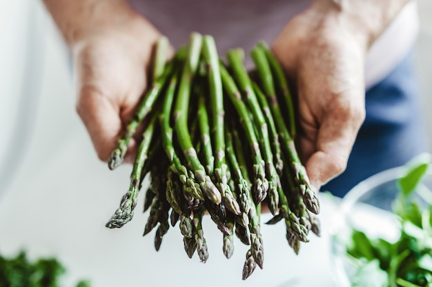 Young man holding fresh asparagus