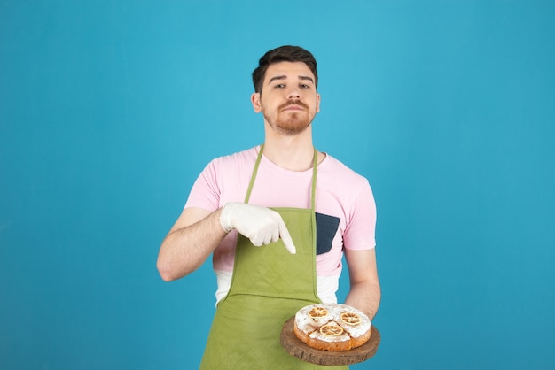 Giovane che tiene torta fresca e punta il dito contro di essa.
