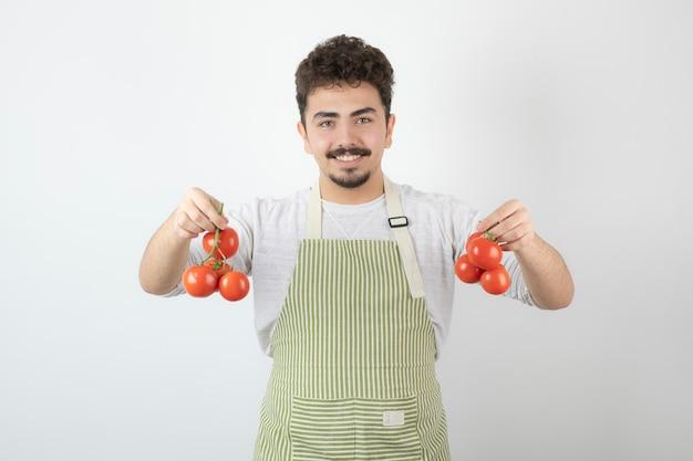 손으로 신선한 토마토를 들고 카메라에 웃 고 젊은 남자.