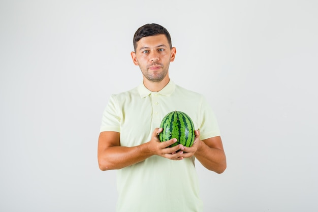 Young man holding fresh watermelon in t-shirt and looking glad.