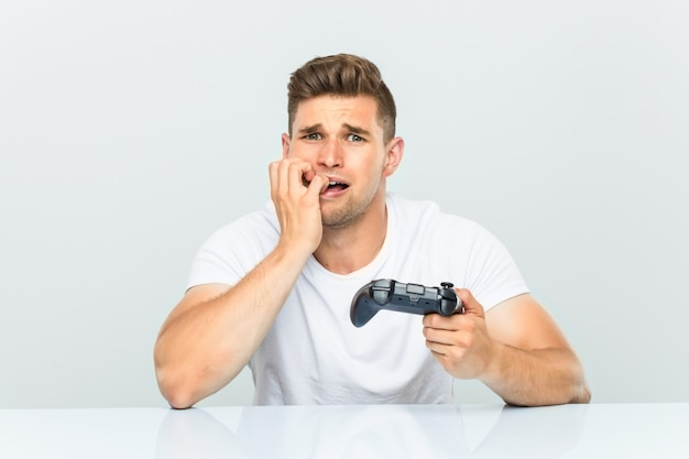 Young man holding a game controller biting fingernails, nervous and very anxious.