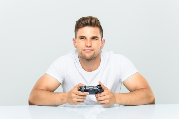Young man holding a game controller happy, smiling and cheerful.