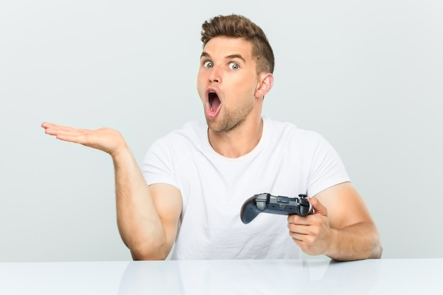Young man holding a game controller impressed holding copy space on palm.