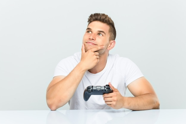 Young man holding a game controller looking sideways with doubtful and skeptical expression.