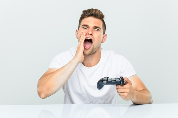 Young man holding a game controller shouting excited to front.