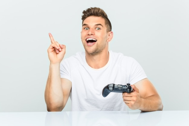 Young man holding a game controller smiling cheerfully pointing with forefinger away.