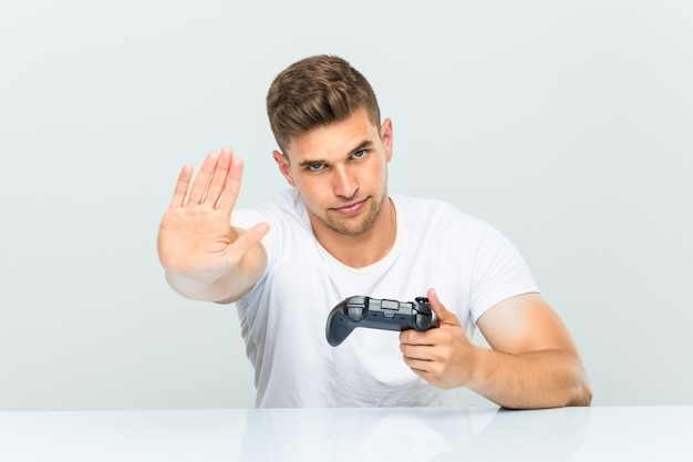 Young man holding a game controller standing with outstretched hand showing stop sign