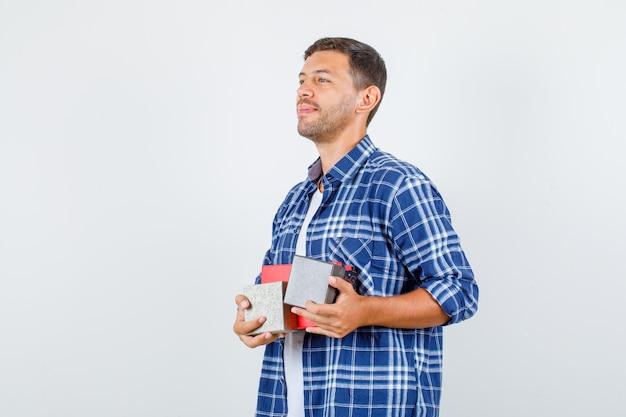 Молодой человек, держащий подарочные коробки в рубашке и смотрящий с надеждой. .