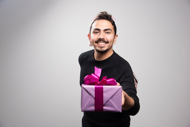 A young man holding a gift box over a gray wall.