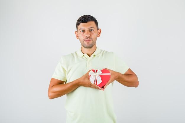 若い男が彼の心にtシャツのギフトボックスを保持