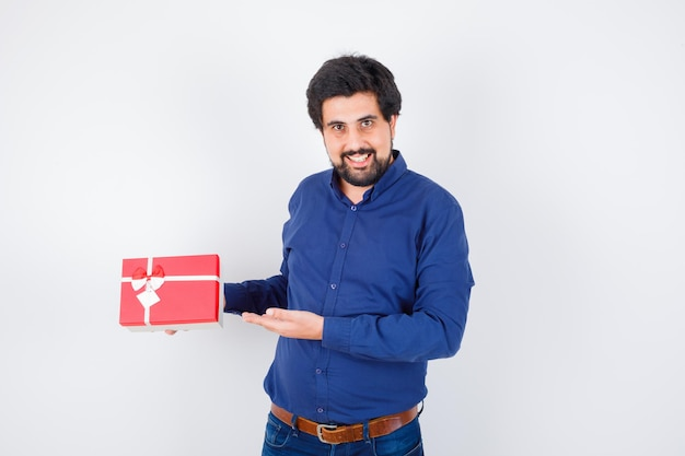 Young man holding gift box and pointing to it in blue shirt and jeans and looking optimistic , front view.