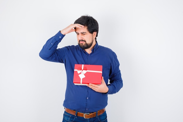 Young man holding gift box and putting hand on forehead while closing eyes in blue shirt and jeans and looking tired. front view.