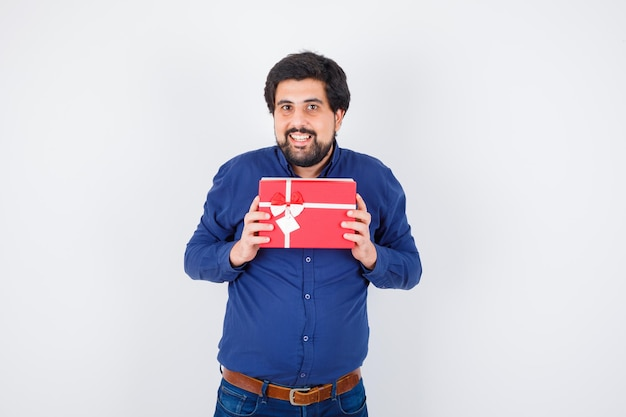 Young man holding gift box with both hands in blue shirt and jeans and looking optimistic. front view.