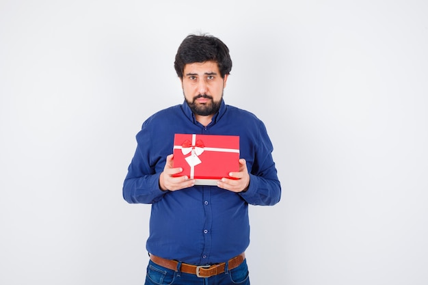 Young man holding gift box with both hands in blue shirt and jeans and looking serious , front view.