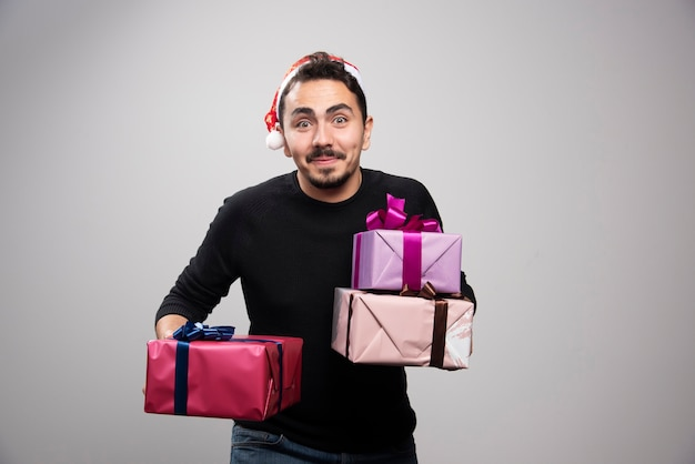A young man holding gift boxes over a gray wall.