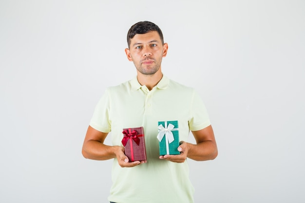 Young man holding gift boxes in t-shirt