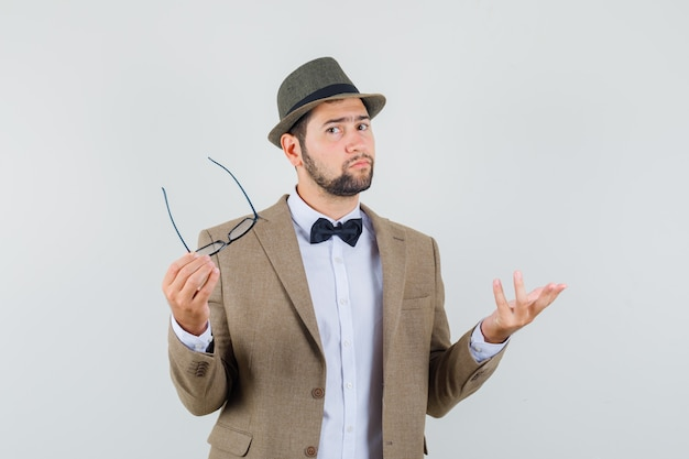 Молодой человек держит очки в костюме, шляпе и недоумевает, вид спереди.