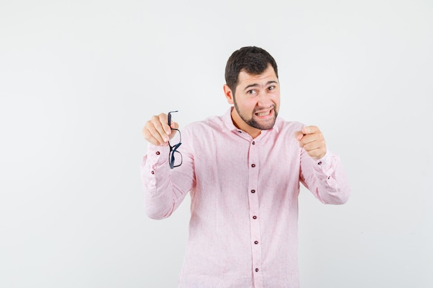 Giovane che tiene i vetri mentre indica alla macchina fotografica in camicia rosa e che sembra arrabbiato