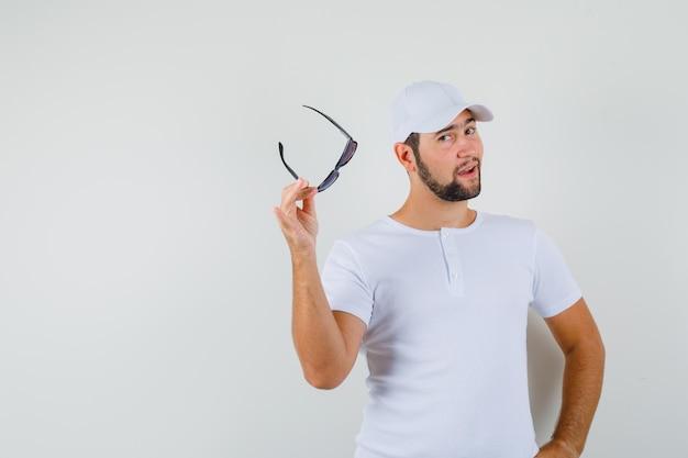 Tシャツ、キャップでポーズをとって自信を持って見ながら眼鏡を保持している若い男。正面図。テキスト用のスペース