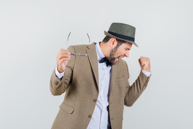 Giovane che tiene i vetri con il gesto del vincitore in vestito, cappello e che sembra riuscito, vista frontale.
