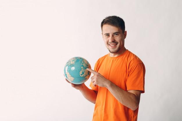 Молодой человек держит глобус в руке и указывая пальцем. туризм и выбор концепции путешествия.
